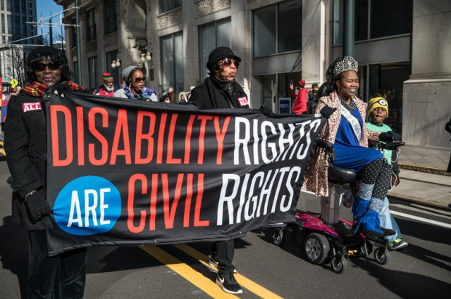 "three African-American women carry a banner reading ""Disability Rights are Civil Rights,"" including a woman with a crown and motorized chair"
