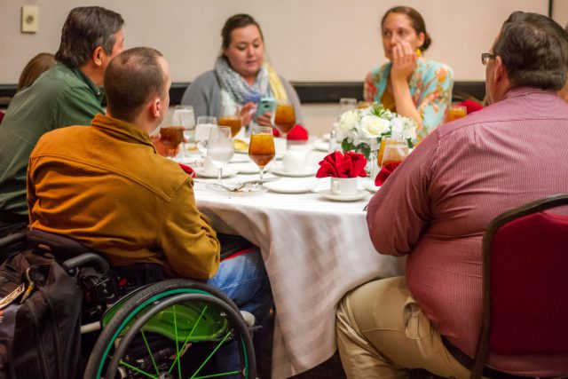 A group of people are seated around a table eating. One man is using a wheelchair.