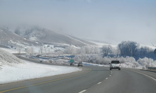 winter scene of a freeway running past trees and a mountain in a rural area