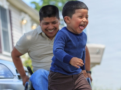 a smiling man in a wheelchair follows behind a laughing young boy running with his tongue out
