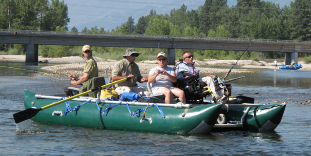 four people (including one man in a wheelchair) go fishing on a raft